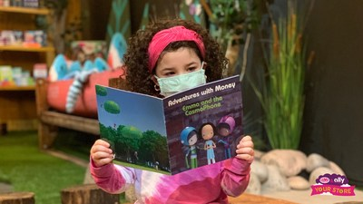 "An elementary school student reads Ally's Adventures in Money book ""Emma and the Cosmo Phone"" at a CAMP store."