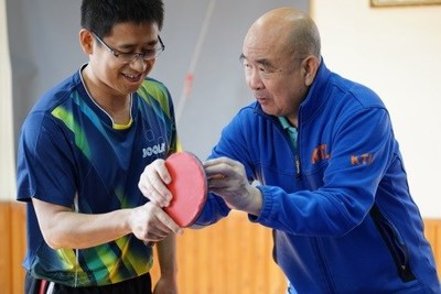 Liang Geliang trains an amateur player in Beijing on February 3 (PHOTO BY ZHANG WEI)