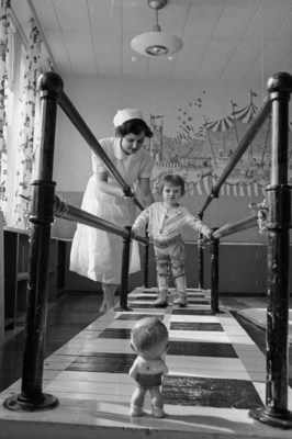 Mrs. E. Marr, physiotherapist, with Gifford, 2 1/2 yrs old, at the walking bars in the polio clinic at the Sudbury General Hospital, courtesy of Library and Archives Canada (CNW Group/Public Health Agency of Canada)